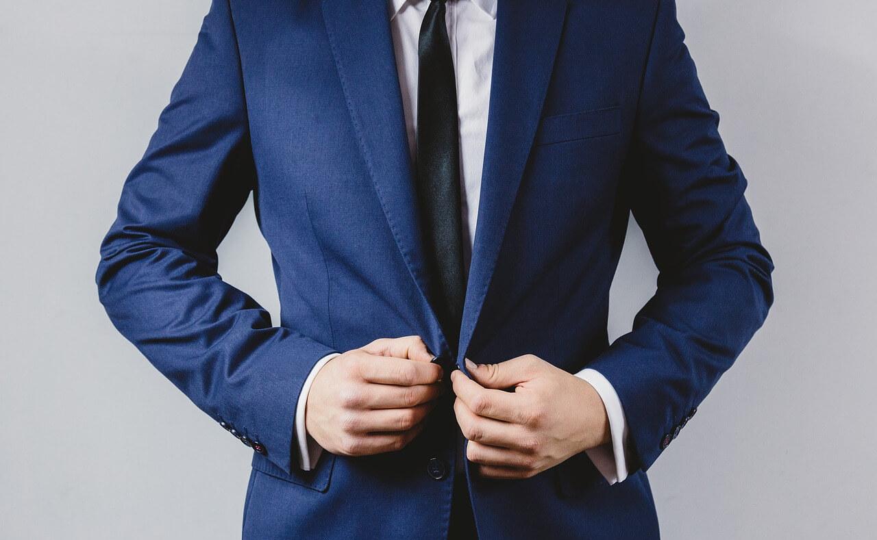 スーツのボタンをしめる男性